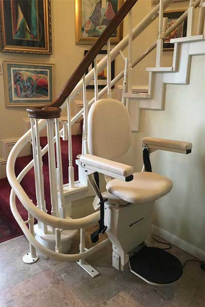Harmar double tube curved stairlift on white stairs